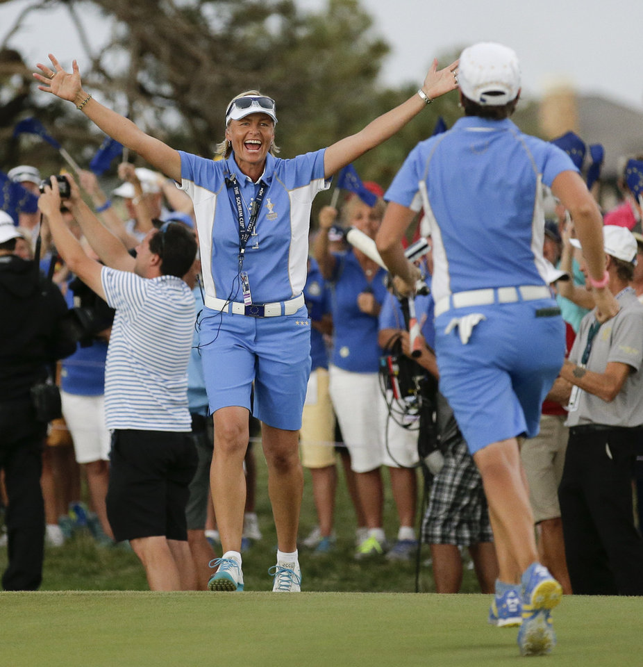 Photo - Europe's captain Liselotte Neumann, left, of Sweden, greets Europe's Catriona Matthew, of Scotland, after they win Solheim Cup golf tournament against the United States, Sunday, Aug. 18, 2013, in Parker, Colo. (AP Photo/Chris Carlson)