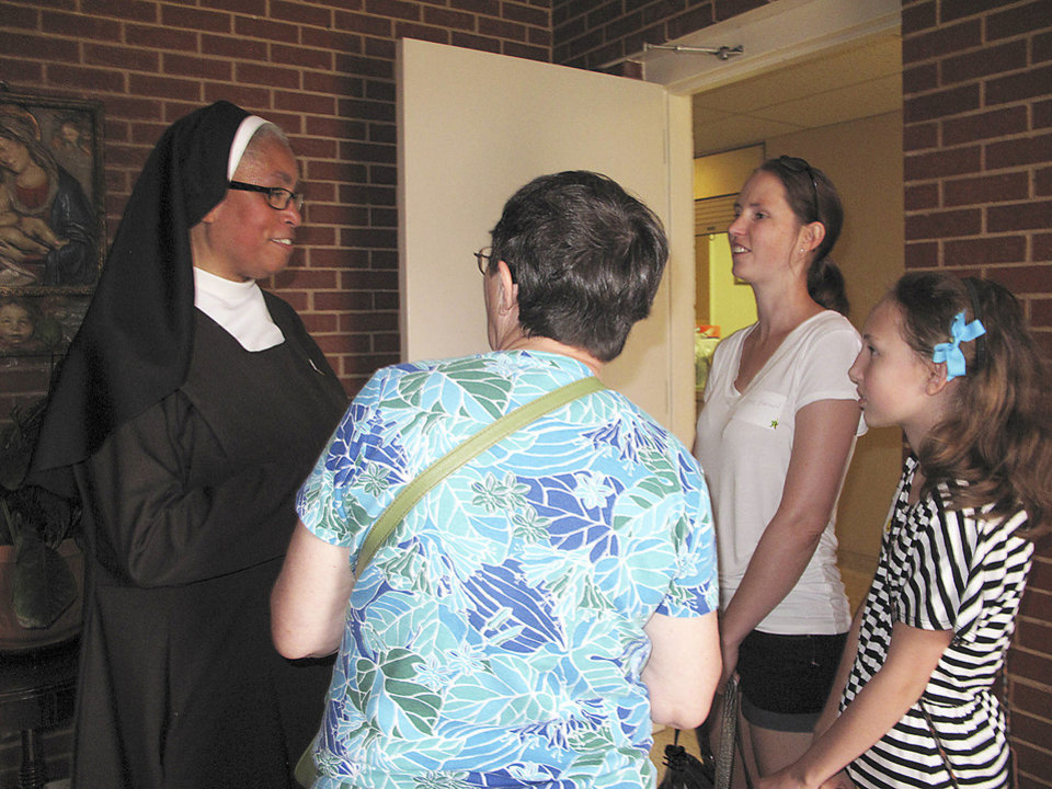 Photo - Sister Veronica Higgins, principal of Villa Teresa School, chats with Leslye Pratt, Pratt's daughter Katie Brown and Brown's daughter Mali Smith, 12, during the Carmelite Sisters of St. Therese's 95th anniversary celebration at the school and Villa Teresa Convent in Oklahoma City. Both Brown and Smith were students at Villa Teresa School. Photo by Carla Hinton, The Oklahoman