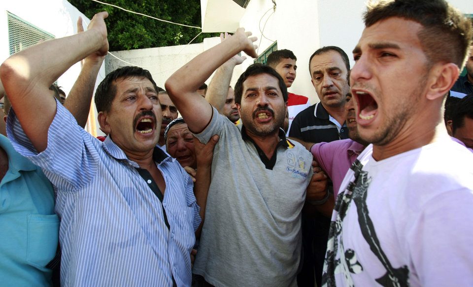 Photo - Palestinians chant slogans as mourners carry the body of Tamer Sammour, 22, during his funeral in the West Bank village of Deir al-Gsoun near Tulkarem town on Friday, Aug. 1, 2014. Sammour was shot and killed during clashes with Israeli troops near Tulkarem, following a protest against the war in the Gaza Strip, Palestinian security sources said. (AP Photo/Mohammed Ballas)