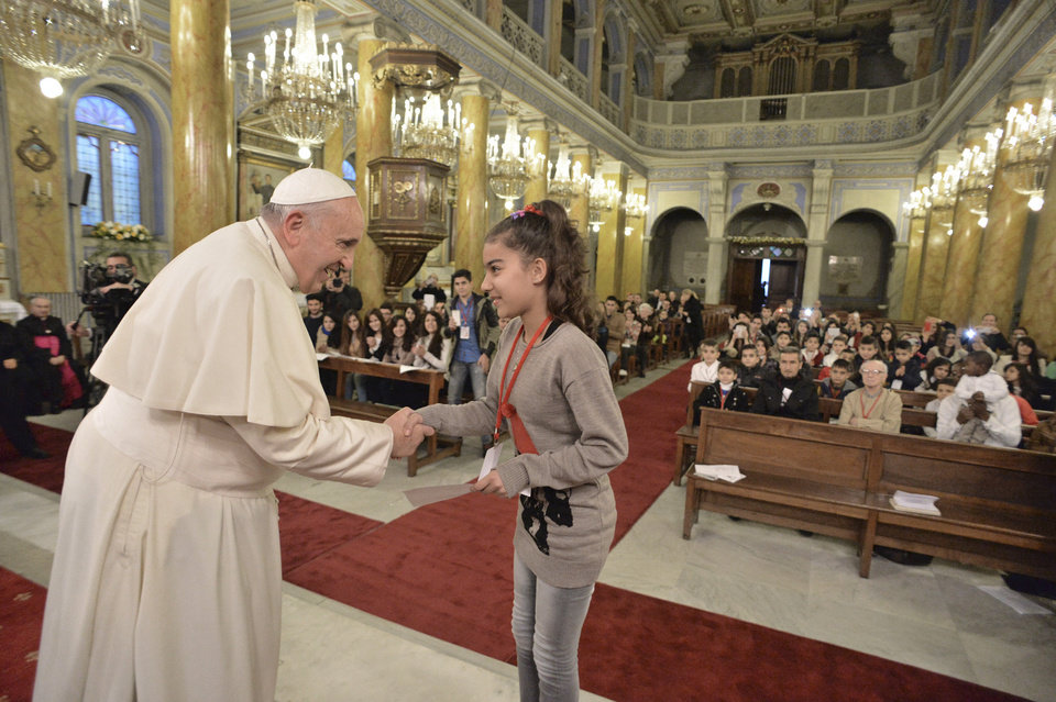 Photo - In this photo provided by Vatican newspaper L'Osservatore Romano, Pope Francis, left, meets with refugee kids in Istanbul, Turkey, Sunday, Nov. 30, 2014. Francis kicked off his final day in Turkey with a lengthy, two-hour liturgy alongside Ecumenical Patriarch Bartholomew I in the Orthodox Church of St. George, where incense mingled with hypnotic chants and prayers on an important feast day for the Orthodox Church. (AP Photo/Osservatore Romano, ho)