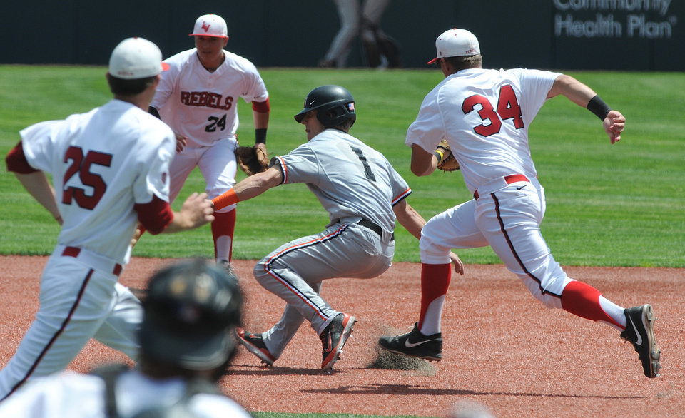 Photo - Oregon State's Andy Peterson (1) is surrounded in a rundown by UNLV's Patrick Armstrong (34), Kenny Oakley (25) and A. J. Hernandez (24) during an NCAA college baseball regional tournament game in Corvallis, Ore., Sunday, June 1, 2014. (AP Photo/Mark Ylen)