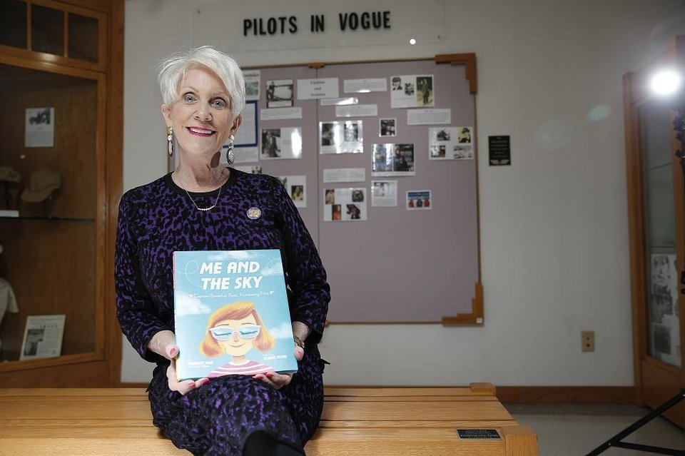 Photo - Beverley Bass poses with her childrens's book at the 99s Museum of Women Pilots in Oklahoma City,Tuesday, Jan. 21, 2020.  [Sarah Phipps/The Oklahoman]