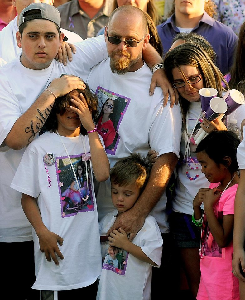 Photo - File - In this Tuesday, April 30, 2013 file photo, the family of slain 8-year-old girl Leila Fowler attend a vigil held for her at Jenny Lind Elementary School in Valley Springs, Calif.  Leila's father, Barney Fowler, center, stands with Leila's mother Crystal Walters, right, at his shoulder. The father of a 12-year-old boy arrested in the stabbing death of his 8-year-old sister says he believes his son is innocent until he is shown evidence that proves otherwise. Barney Fowler said on Monday May 13, 2013 that the family is standing behind the boy