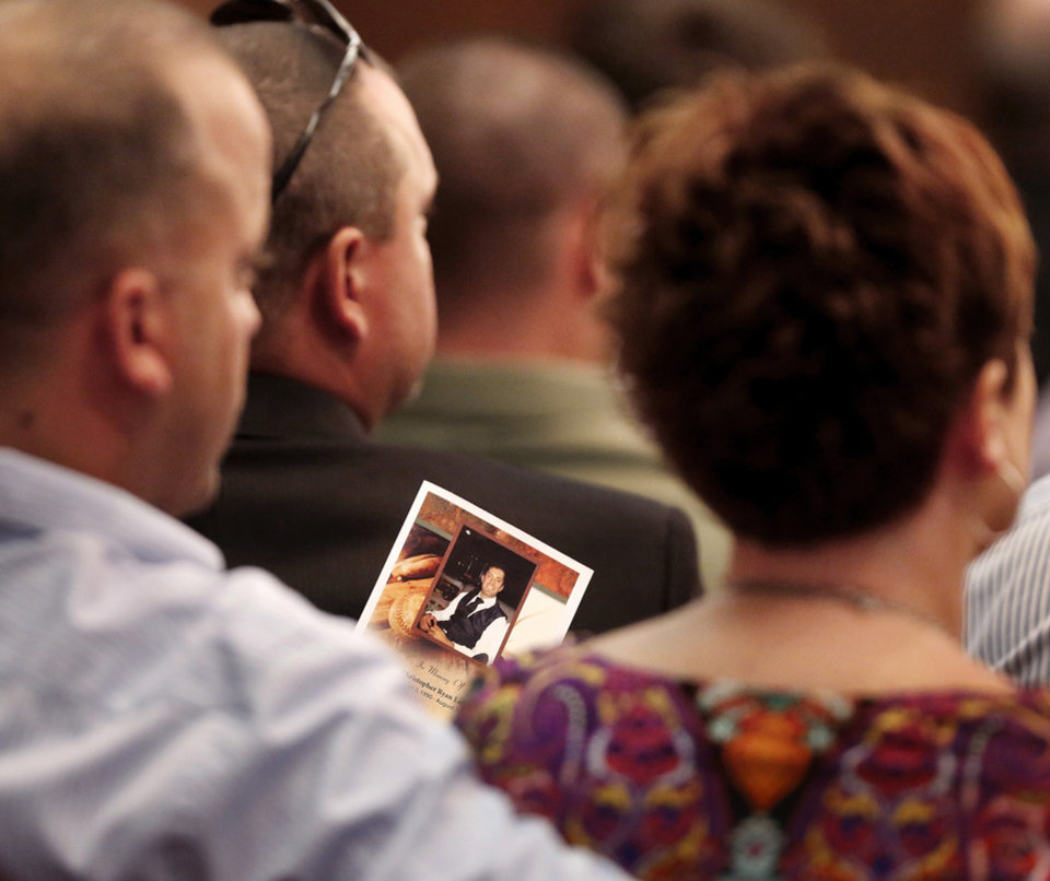 Photo - A man holds a program with a photo of Christopher Ryan Lane on the cover. About 200 friends, many of them former college baseball teammates,  attended a memorial service at Oklahoma Christian University  Saturday afternoon, Aug. 24, 2013, to remember student-athlete Christopher Lane during a memorial service for the East Central University athlete who was gunned down while jogging in Duncan, Okla. last week.   Photo  by Jim Beckel, The Oklahoman.