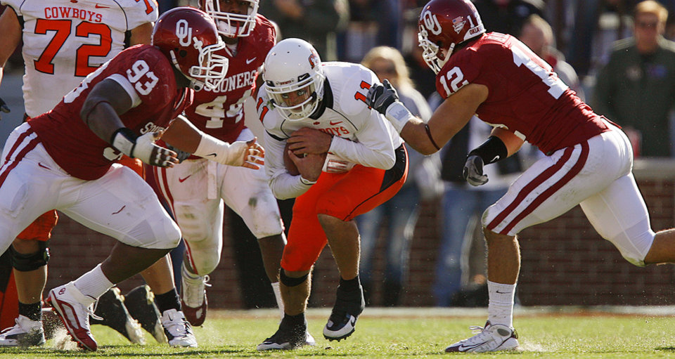 Photo - Oklahoma's Gerald McCoy (93) and Austin Box (12) close in to bring down OSU's Zac Robinson (11) during the second half of the Bedlam college football game between the University of Oklahoma Sooners (OU) and the Oklahoma State University Cowboys (OSU) at the Gaylord Family-Oklahoma Memorial Stadium on Saturday, Nov. 28, 2009, in Norman, Okla.Photo by Chris Landsberger, The Oklahoman