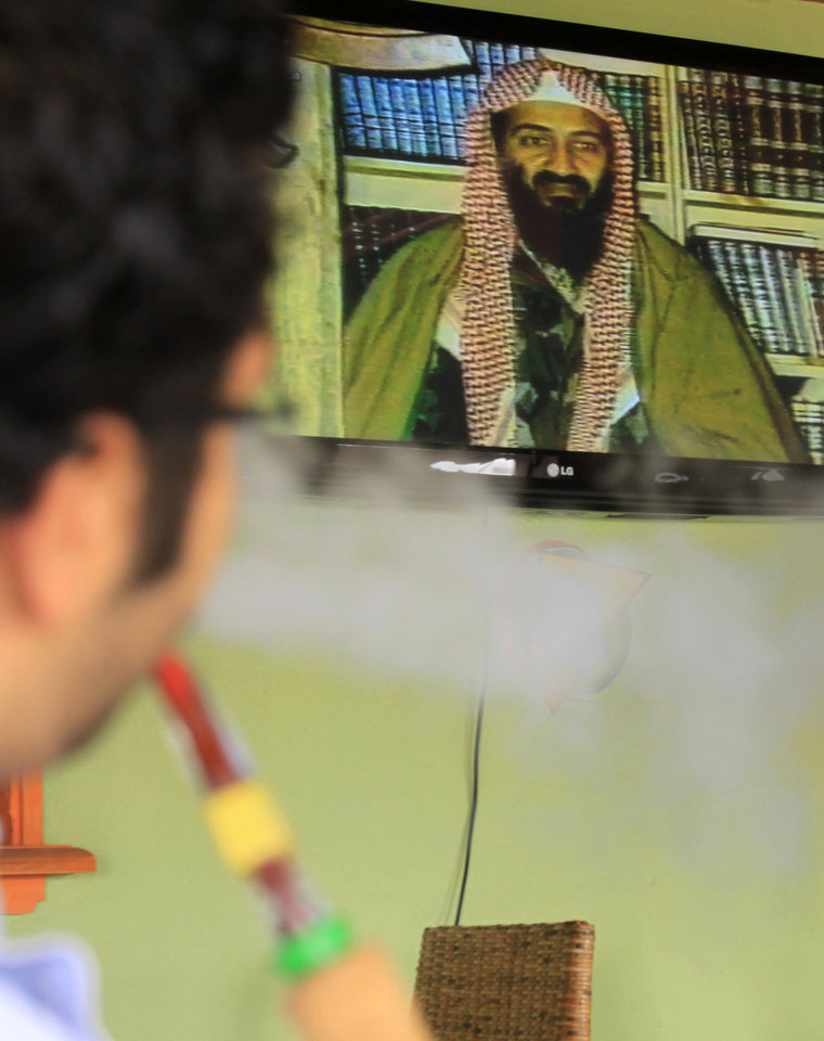 Photo - A Bahraini man smokes a water-pipe while watching a TV news report on the killing of Al-Qaida leader Osama bin Laden,  at a coffee shop in Sitra, Bahrain, on Monday, May 2, 2011.   al-Qaida chief  Osama bin Laden was slain in his fortress-like compound in Abbottabad, Pakistan, early Monday in a firefight with U.S. forces, ending a manhunt that spanned a decade. (AP Photo/Hasan Jamali) ORG XMIT: XHJ102
