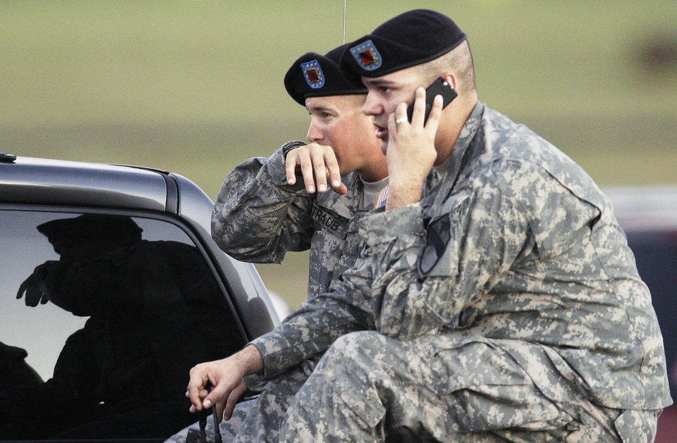 Photo - Spc. Ryan Howard of Niles, Mich., right, and Spc.  David Straub of Ardmore wait Thursday for news of fellow soldiers at Fort Hood. AP PHOTO