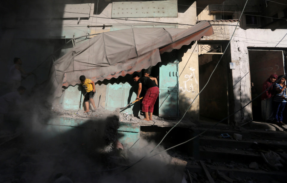 Photo - Palestinians inspect the rubble of a house after it was hit by an Israeli missile strike in Gaza City, Friday, July 18, 2014. Israeli troops pushed deeper into Gaza on Friday to destroy rocket launching sites and tunnels, firing volleys of tank shells and clashing with Palestinian fighters in a high-stakes ground offensive meant to weaken the enclave's Hamas rulers.(AP Photo/Hatem Moussa)