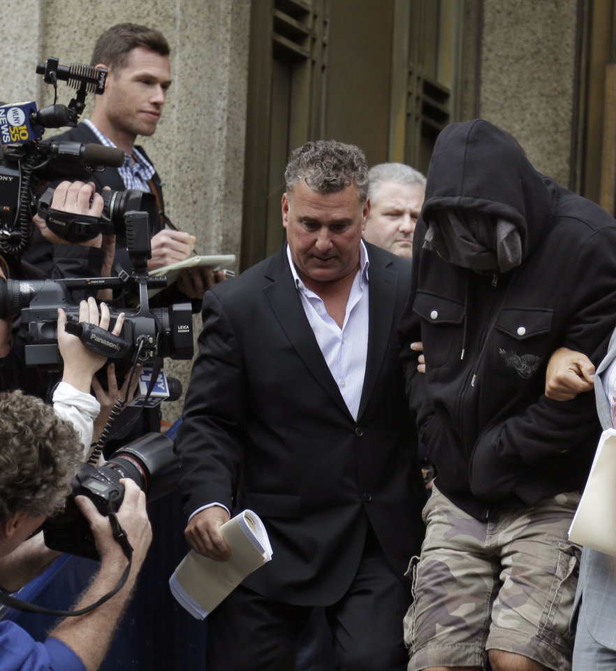 Photo - Wojciech Braszczok, right, with face covered, leaves the courthouse in New York, Wednesday, Oct. 9, 2013. Braszczok, an undercover police detective, was charged with gang assault in a motorcycle rally that descended into violence in New York. (AP Photo/Seth Wenig)