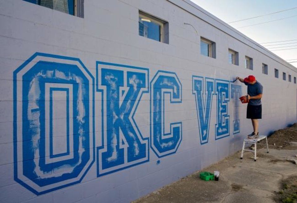 Photo -  Ace Walker paints the logo of the new OKC Vet Campus at 601 W Reno Ave. The facility will open June 1 and offer services as a veterinarian clinic, boarding kennels, training and daycare, pet store, grooming and bath salon and agility training. [Chris Landsberger/The Oklahoman]