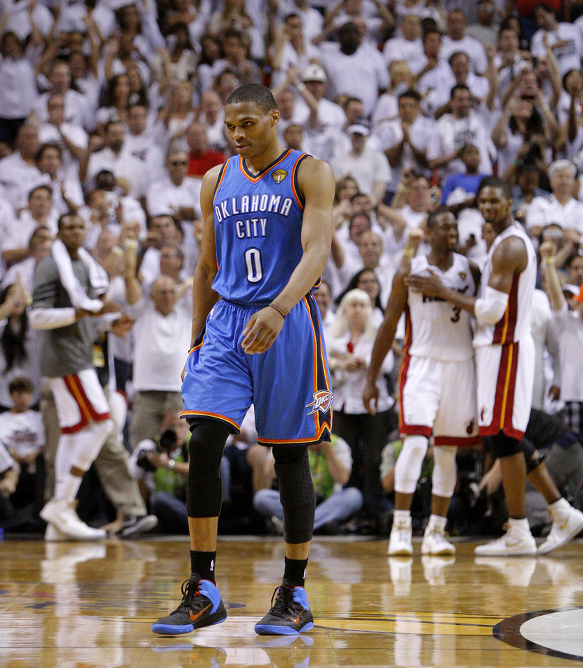 Oklahoma City's Russell Westbrook (0) walks off the court as Miami's Dwyane Wade (3) and Chris Bosh (1) celebrate after Game 3 of the NBA Finals between the Oklahoma City Thunder and the Miami Heat at American Airlines Arena, Sunday, June 17, 2012. Oklahoma CIty lost 91-85. Photo by Bryan Terry, The Oklahoman