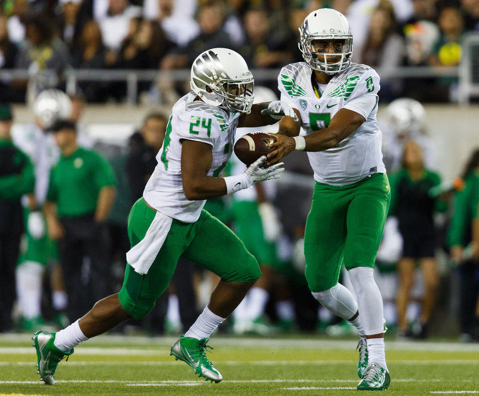 Photo - Oregon quarterback Marcus Mariota (8) hands off to running back Thomas Tyner (24) during the second quarter of an NCAA college football game against South Dakota in Eugene, Ore., Saturday, Aug. 30, 2014. (AP Photo/Ryan Kang)