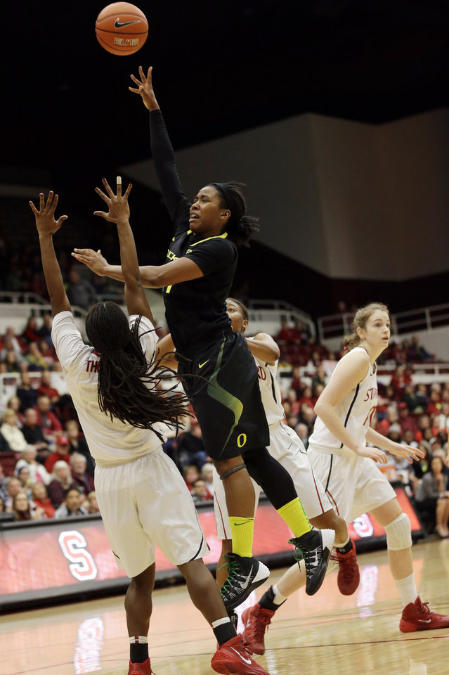 Photo - Oregon's Chrishae Rowe, center, shoots over Stanford 's Lili Thompson, left, during the first half of an NCAA college basketball game on Friday, Jan. 3, 2014, in Stanford, Calif. (AP Photo/Marcio Jose Sanchez)