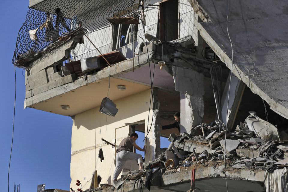 Photo - Palestinians inspect damages of the el-Yazje family apartment building which was destroyed following an overnight Israeli missile strike in Gaza City, Thursday, July 17, 2014. The Israeli military says it has struck 37 targets in Gaza ahead of a five-hour humanitarian cease-fire meant to allow civilians to stock up after 10 days of fighting. The Gaza Interior Ministry says four people were killed and that a 75-year-old woman died of wounds from the day before. The Israeli army says Hamas fired 11 rockets at Israel early Thursday. Palestinian health officials say that in total, at least 225 Palestinians have been killed. On the Israeli side, one man was killed since July 8. (AP Photo/Lefteris Pitarakis)