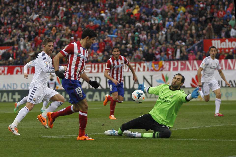 Photo - Atletico's Diego Costa, left, in action with Real goalkeeper Diego Lopez, right, during a Spanish La Liga soccer match between Atletico de Madrid and Real Madrid at the Vicente Calderon stadium in Madrid, Spain, Sunday, March 2, 2014. (AP Photo/Gabriel Pecot)