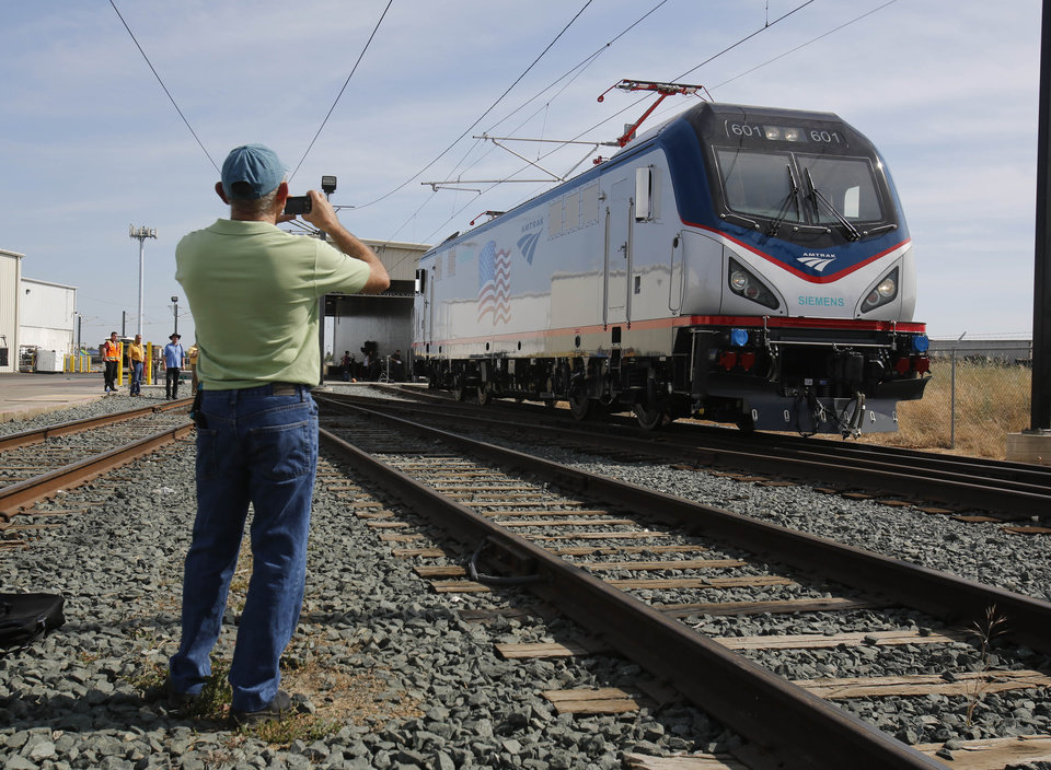 Photo - In this photo taken Saturday, May 11, 2013, Dave Ward, vice president of Locomotives for the Siemens Rail Systems,  takes a picture of one of the new Amtrak Cities Sprinter Locomotive built by Siemens  in Sacramento, Calif. The new electric locomotive, one of three of 70 to be built,  will run on the Northeast intercity rail lines and  replace Amtrak locomotives that have been in service for 20 to 30 years.(AP Photo/Rich Pedroncelli)