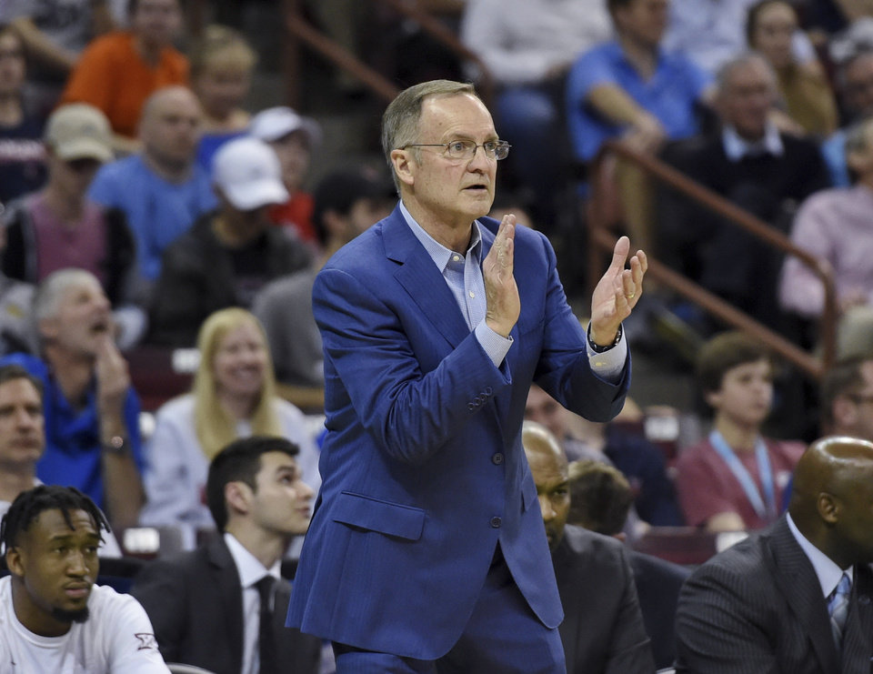 Photo - Oklahoma coach Lon Kruger applauds his team during the second half of a second-round men's college basketball game against Virginia in the NCAA Tournament in Columbia, S.C., Sunday, March 24, 2019. (AP Photo/Richard Shiro)