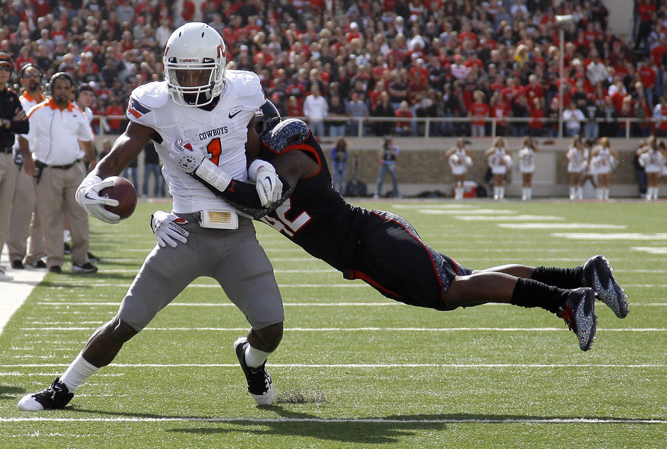 Photo - Oklahoma State Cowboys's Joseph Randle (1) tries to get by Daniel Cobb (42) during a college football game between Texas Tech University (TTU) and Oklahoma State University (OSU) at Jones AT&T Stadium in Lubbock, Texas, Saturday, Nov. 12, 2011.  Photo by Sarah Phipps, The Oklahoman  ORG XMIT: KOD