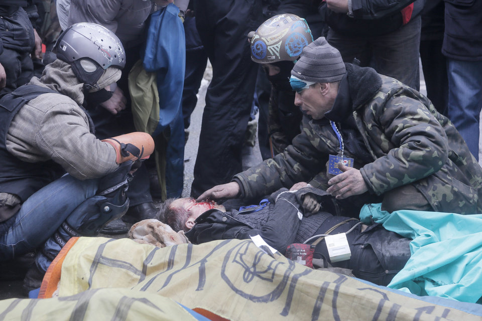 Photo - An activist closes a victim's eyes while others pay respects to protesters who were killed in clashes with police in Kiev's Independence Square, the epicenter of the country's current unrest, Thursday, Feb. 20, 2014. Fierce clashes between police and protesters in Ukraine's capital have shattered the brief truce Thursday and an Associated Press reporter has seen dozens bodies laid out on the edge of the protest encampment.  (AP Photo/Efrem Lukatsky)