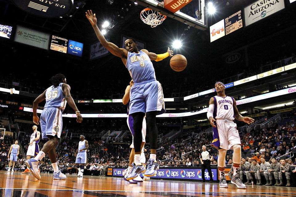 Photo -   Denver Nuggets' Andre Iguodala (9) reacts after dunking the ball as Phoenix Suns' Michael Beasley (0) watches during the first half of an NBA basketball game, Monday, Nov. 12, 2012, in Phoenix. (AP Photo/Ross D. Franklin)