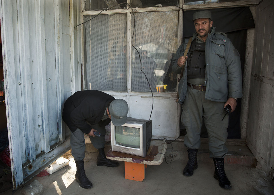 Photo - Afghan policemen turn on a TV to tune into the Loya Jirga session at their checkpoint outside the venue where thousands of prominent Afghans gather to debate a contentious security agreement with the United States in the Afghan capital, Thursday, Nov. 21, 2013. Afghanistan's president Hamid Karzai said he backs a security deal with the United States but told the gathering of elders that if they and parliament approve the agreement it should be signed after next spring's elections. Without the agreement the United States previously warned that it will remove all its troops by the end of 2014.  (AP Photo/Anja Niedringhaus)