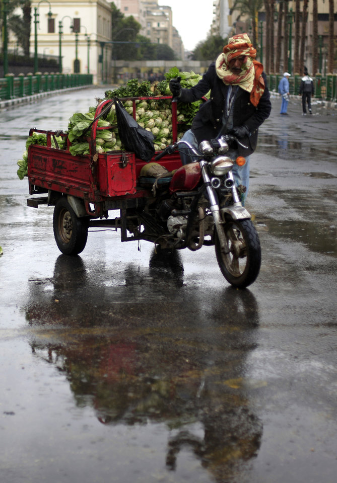 Photo - An Egyptian street vendor sells vegetables on a motorbike during a rally in Tahrir Square, Cairo, Egypt, Friday, Feb. 1, 2013. Thousands of Egyptians marched across the country, chanting against the rule of the Islamist President Mohammed Morsi, in a fresh wave of protests Friday, even as cracks appeared in the ranks of the opposition after its political leaders met for the first time with the rival Muslim Brotherhood. (AP Photo/Khalil Hamra)