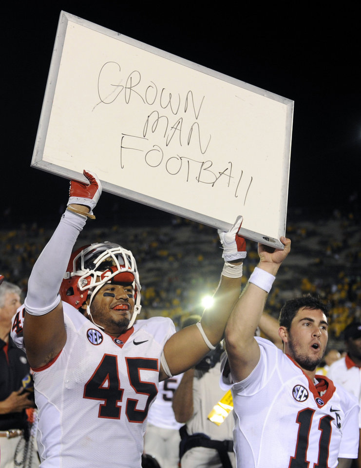 Georgia's Christian Robinson, left, and teammate Aaron Murray hold up a sign following Georgia's 41-20 victory over Missouri in the Tigers' first SEC game in Columbia, Mo. AP PHOTO