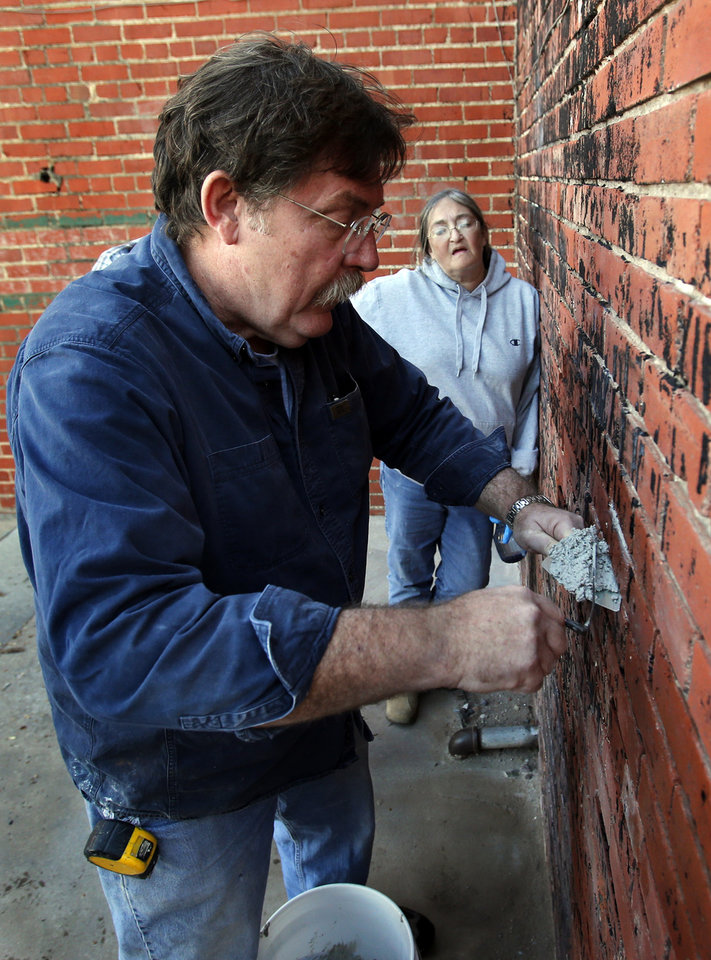 Bob Yapp teaches residents how to make masonry repairs on a downtown building on Saturday, Nov. 17, 2012 in Norman, Okla.  Yapp is a nationally recognized historic preservation expert who is leading a workshop on masonry repair.  Emily Ryther looks on.  Photo by Steve Sisney, The Oklahoman