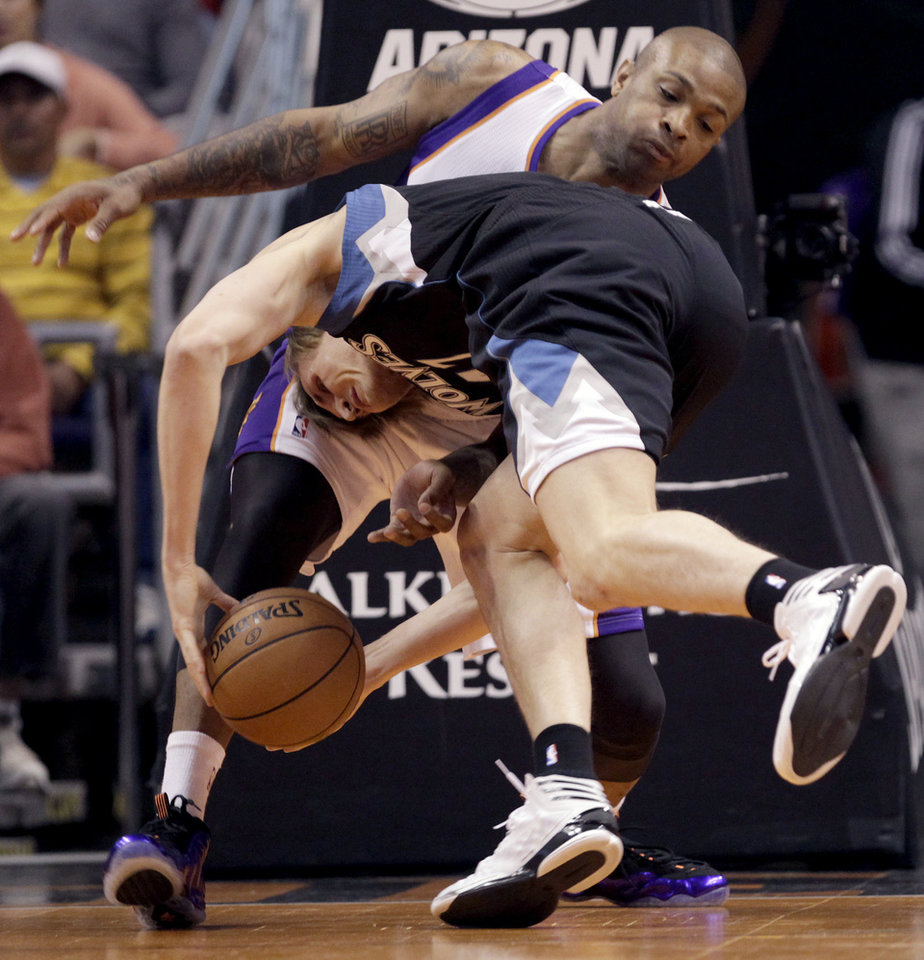 Minnesota Timberwolves' Andrei Kirilenko, bottom, of Russia, falls into Phoenix Suns' P.J. Tucker (17) during the first half of an NBA basketball game, Tuesday, Feb. 26, 2013, in Phoenix. (AP Photo/The Arizona Republic, Michael Chow)  MARICOPA COUNTY OUT; MAGS OUT; NO SALES
