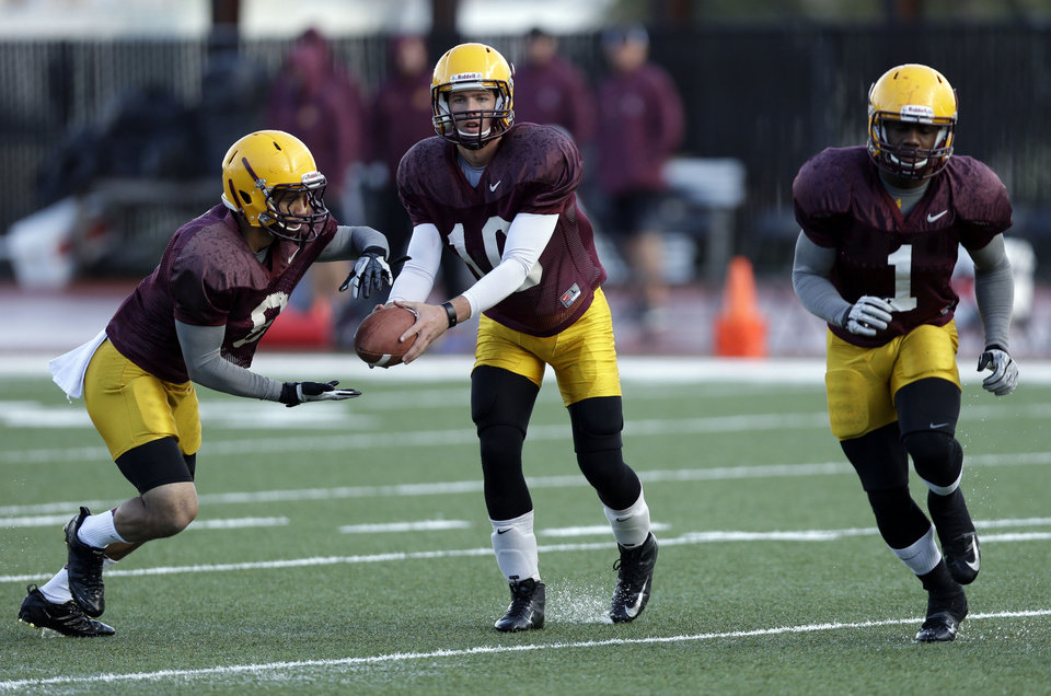 Photo - Arizona State quarterback Taylor Kelly (10) hands off to running back D.J. Foster, left, as running back Marion Grice runs along side during practice in San Francisco, Wednesday, Dec. 26, 2012. Arizona State plays Navy in the Fight Hunger Bowl NCAA college football game in San Francisco on Saturday.  (AP Photo/Marcio Jose Sanchez)