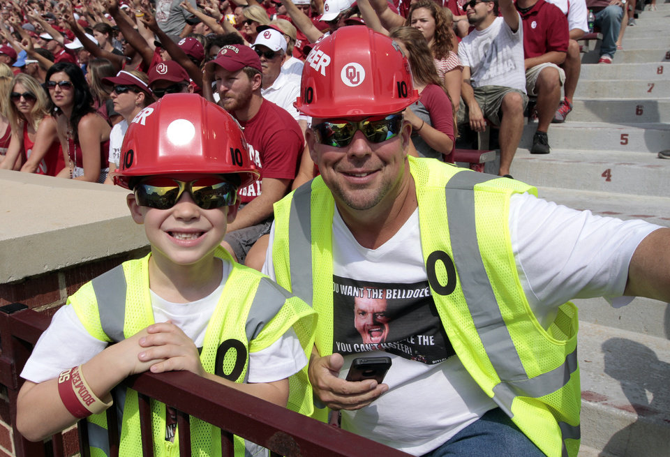 Photo - Bill Kauffman, Tulsa, and son Joey, 6, wear Bell Dozer apparel, during a college football game between the University of Oklahoma Sooners (OU) and the Tulsa Golden Hurricane (TU) at Gaylord Family-Oklahoma Memorial Stadium in Norman, Okla., on Saturday, Sept. 14, 2013. Photo by Steve Sisney, The Oklahoman