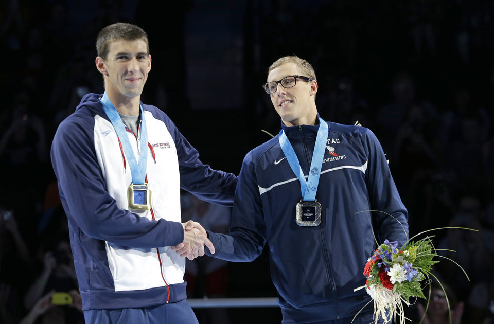 Photo -   Michael Phelps, left, and Tyler McGill shake hands during the medal ceremony for the men's 100-meter butterfly at the U.S. Olympic swimming trials on Sunday, July 1, 2012, in Omaha, Neb. (AP Photo/Mark Humphrey)