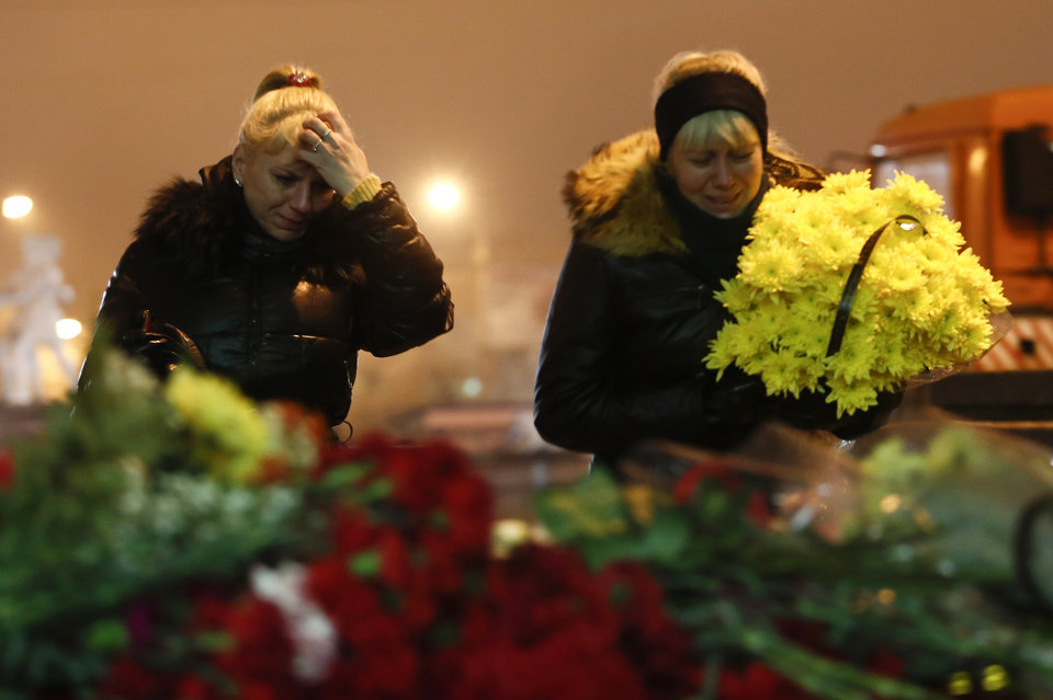 Photo - Women cry laying flowers outside the Volgograd main railway station in Volgograd, Russia, early Monday Dec. 30, 2013. Russian authorities ordered police to beef up security at train stations and other facilities across the country after a suicide bomber killed 14 people on a bus Monday in the southern city of Volgograd.It was the second deadly attack in two days on the city that lies just 400 miles (650 kilometers) from the site of the 2014 Winter Olympics. (AP Photo/Denis Tyrin)