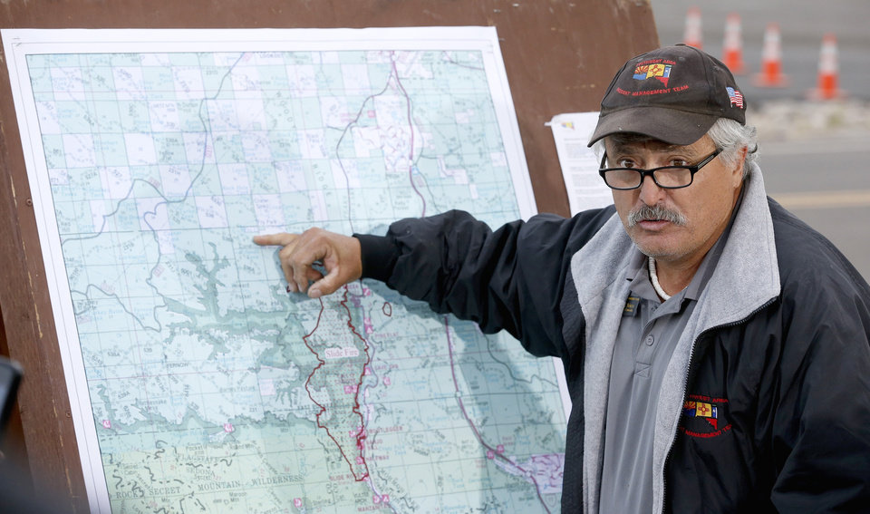 Photo - Fire incident commander Tony Sciacca gives a news briefing on the fire fighting progress on the Slide Fire as it burns up Oak Creek Canyon on Friday, May 23, 2014, in Flagstaff, Ariz.  The fire has burned approximately 7,500 acres and is five percent contained. (AP Photo/Ross D. Franklin)