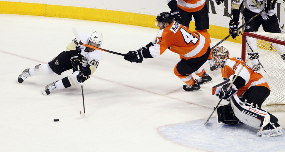 Photo - Pittsburgh Penguins' Brian Gibbons, left, loses his edge and the puck trying to shoot as Philadelphia Flyers' Andrew MacDonald, center, and goalie Steve Mason defend during the third period of an NHL hockey game, Saturday, March 15, 2014, in Philadelphia. The Flyers won 4-0. (AP Photo/Tom Mihalek)