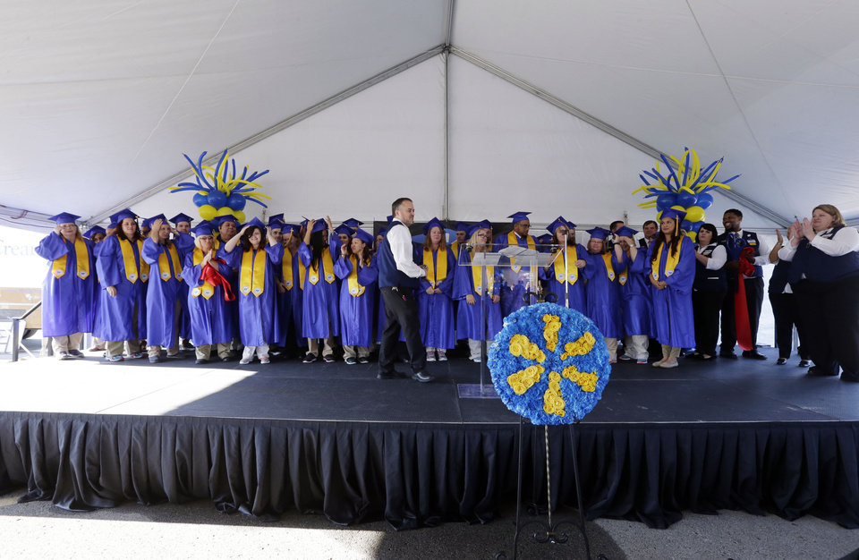 Photo -  Graduates stand on stage during Friday's Walmart Academy graduation at the Walmart Supercenter in Broken Arrow. [CORY YOUNG/Tulsa World]