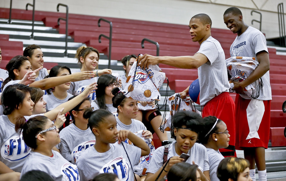 Photo - Russell Westbrook and Reggie Jackson hand out goodie bags to students during a visit by the Oklahoma City Thunder to  U.S. Grant High School to promote physical fitness on Monday, Jan. 28, 2013, in Oklahoma City, Okla.  Photo by Chris Landsberger, The Oklahoman