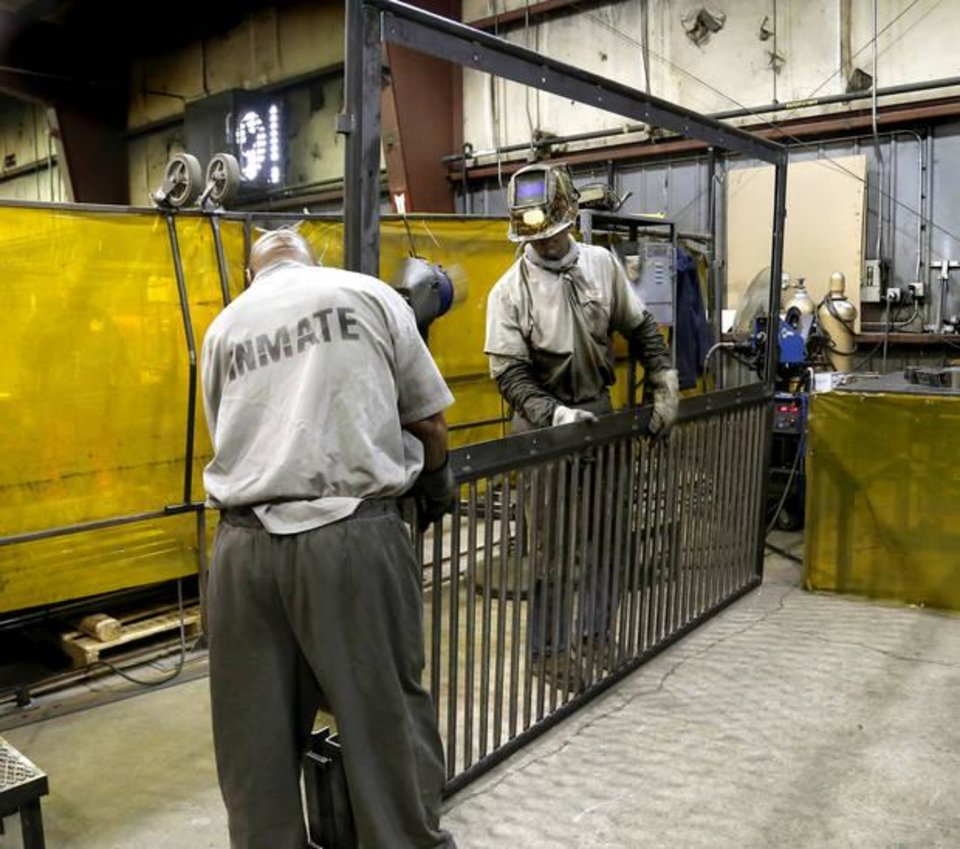 Photo -  These inmates work on livestock fences and gates for the Tulsa County Fairgrounds.