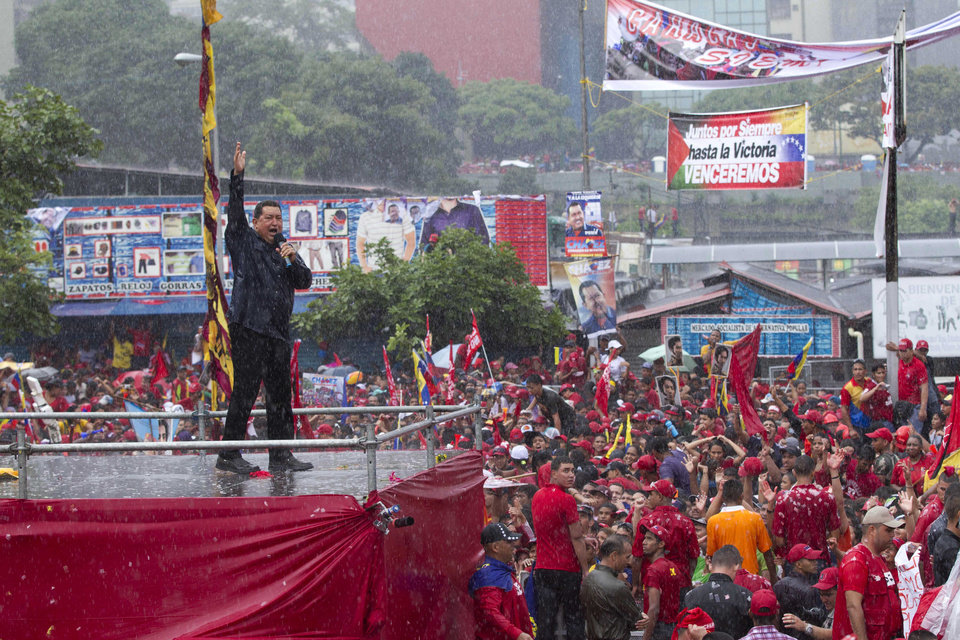 Under pouring rain, Venezuela's President Hugo Chavez, right, delivers a speech during his closing campaign rally in Caracas, Venezuela, Thursday, Oct. 4, 2012. Chavez is running for re-election against opposition candidate Henrique Capriles in presidential elections on Oct . 7. (AP Photo/Ariana Cubillos)