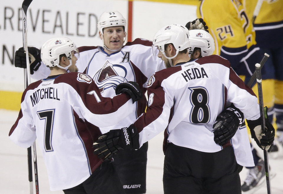 Photo - Colorado Avalanche defenseman Jan Hejda (8), of the Czech Republic, celebrates with John Mitchell (7) and Cody McLeod (55) after Hejda scored against the Nashville Predators in the first period of an NHL hockey game, Saturday, Jan. 18, 2014, in Nashville, Tenn. (AP Photo/Mark Humphrey)