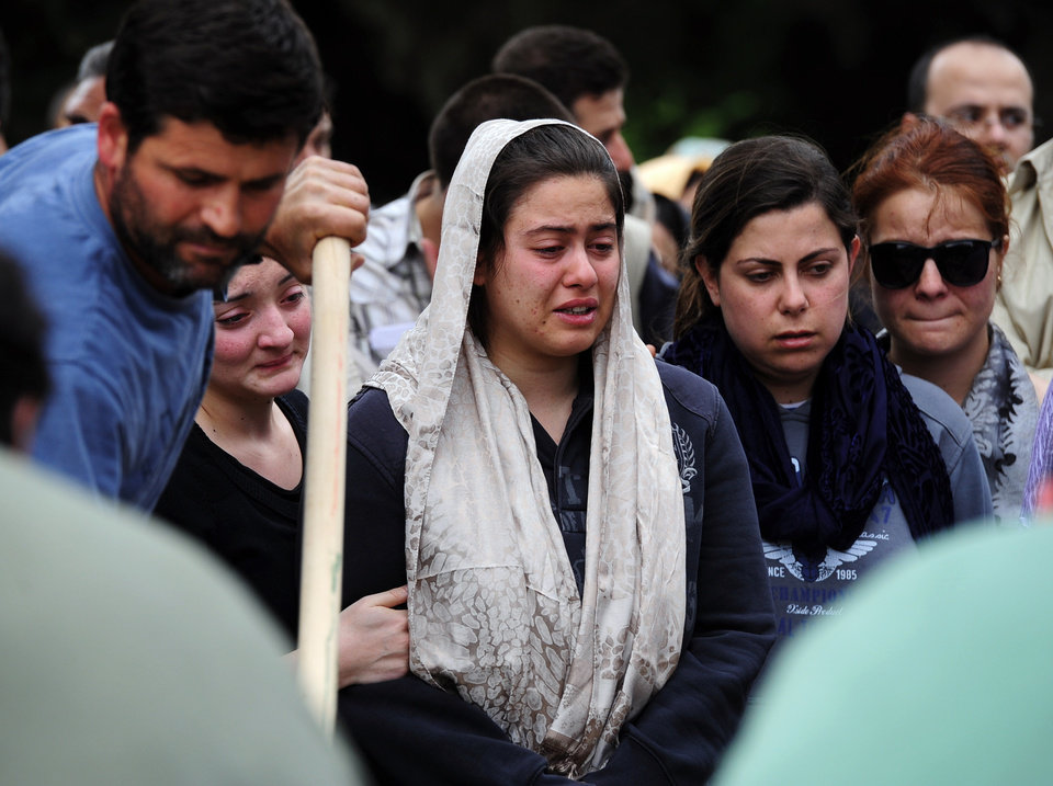 Photo - People attend a mine accident victim's burial in Soma, Turkey, Wednesday, May 14, 2014. Nearly 450 miners were rescued, the mining company said, but the fate of an unknown number of others remained unclear as bodies are still being brought to the surface and burials are underway after one of the world's deadliest mining disasters .(AP Photo/Emre Tazegul)