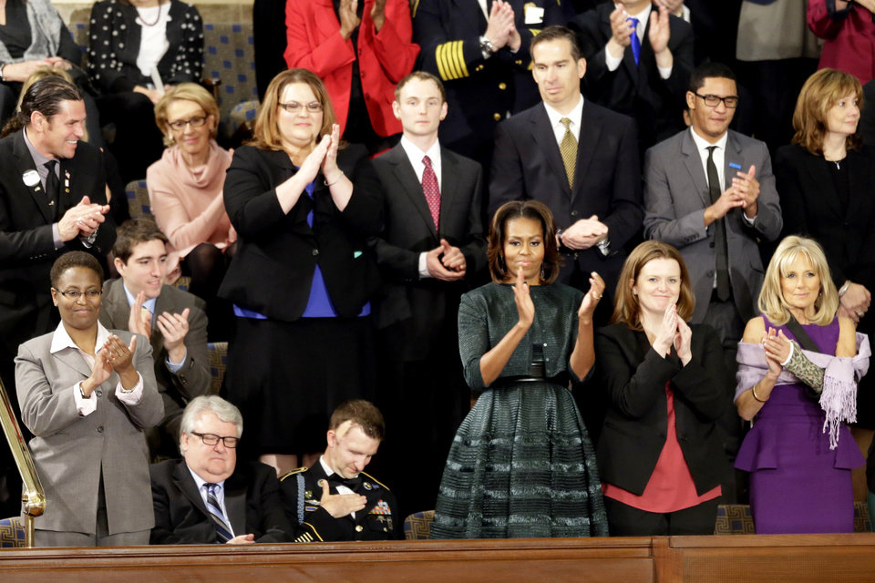 Photo - ** ADDS NAMES* First Lady Michelle Obama and guests applaud during President Barack Obama State of the Union address on Capitol Hill in Washington, Tuesday Jan. 28, 2014. Jill Biden with her left arm in a cast is at far right.  Front row, from left are, Sabrina Simone Jenkins, Craig, Remsburg, Sgt. 1st Class Cory Remsburg, first lady Michelle Obama, Misty DeMars and Jill Biden. Second row, from left are, Jeff Bauman, Carlos Arredondo, Amanda Shelly, Nick Chute, John Soranno, Estiven Rodriguez, and General Motors CEO Mary Barra. (AP Photo/J. Scott Applewhite)