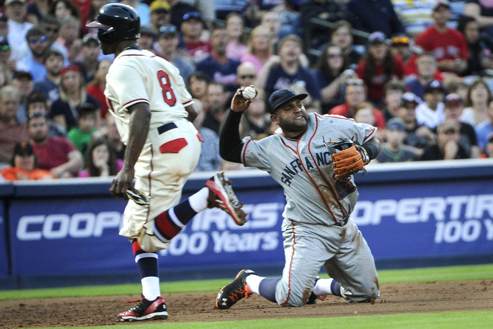 Photo - Atlanta Braves' Justin Upton (8) runs to third base as San Francisco Giants third baseman Pablo Sandoval (48) throws out Evan Gattis at second and a double play is turned on Chris Johnson's ground ball during the second inning of a baseball game, Saturday, May 3, 2014, in Atlanta. (AP Photo/John Amis)