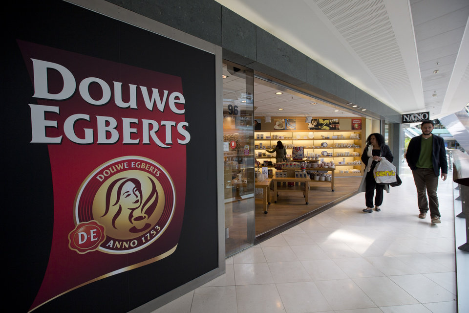 Photo - Two people pass the Douwe Egberts Café at Villa ArenA, a mall which specializes in interior design, on the outskirts of Amsterdam, Netherlands, Wednesday, May 7, 2014. Mondelez International Inc. and D.E. Master Blenders 1753 B.V. are combining their coffee businesses. The business will house coffee brands such as Gevalia and Jacobs from Mondelez and Senseo and Douwe Egberts from D.E. Master Blenders, formerly the Sara Lee coffee business. The new company will be called Jacobs Douwe Egberts and be headquartered in the Netherlands. The combined company will have annual revenue of more than 7 billion U.S. dollars. (AP Photo/Peter Dejong)