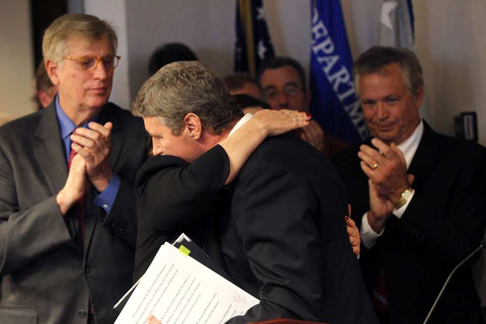 Photo - Jim Letten, U.S. Attorney for the Eastern District, hugs his wife JoAnn as he announces his resignation during a news conference in New Orleans, Thursday, Dec. 6, 2012.  Letten said his resignation is effective Dec. 11 and that he plans to stay on with the department briefly to help with the transition in leadership. (AP Photo/Gerald Herbert)