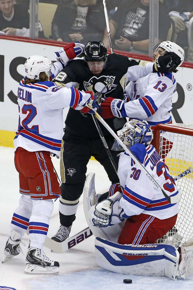 Photo - Pittsburgh Penguins' James Neal (18) is sandwiched between New York Rangers' Carl Hagelin (62) and Daniel Carcillo (13) to keep him from a loose puck in front of Rangers goalie Henrik Lundqvist (30) in the first period of game 2 of a second-round NHL playoff hockey series in Pittsburgh Sunday, May 4, 2014. (AP Photo/Gene J. Puskar)