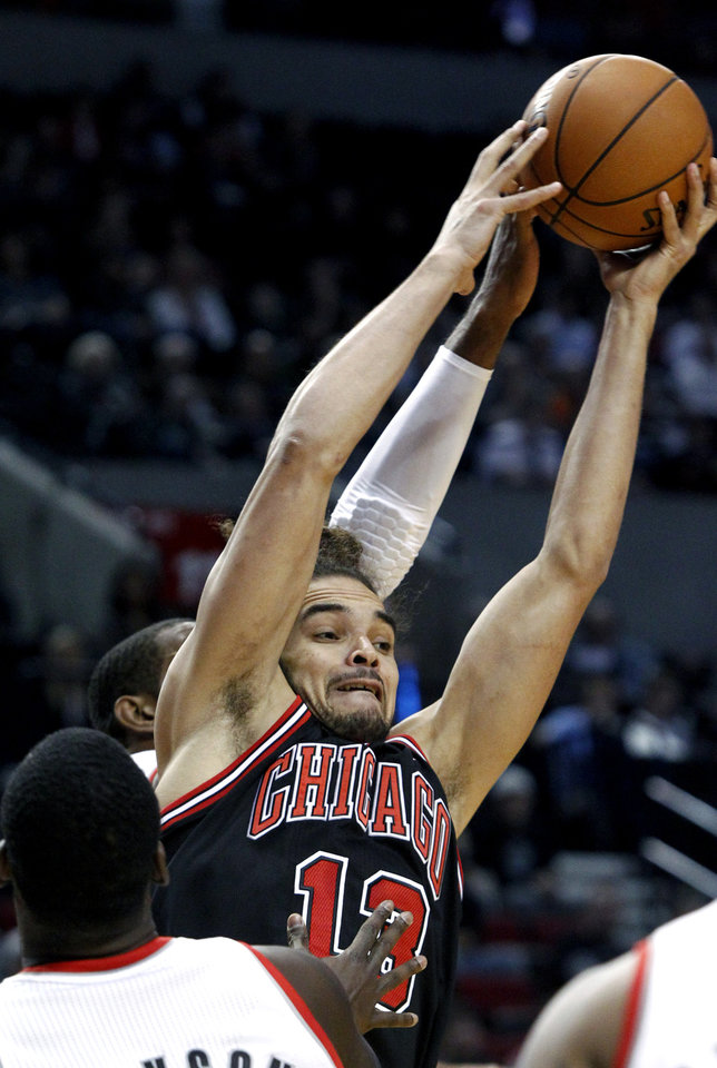 Chicago Bulls center Joakim Noah, right, pulls in an offensive rebound against Portland Trail Blazers forward LaMarcus Aldridge during the first quarter of their NBA basketball game in Portland, Ore., Sunday, Nov. 18, 2012. (AP Photo/Don Ryan)