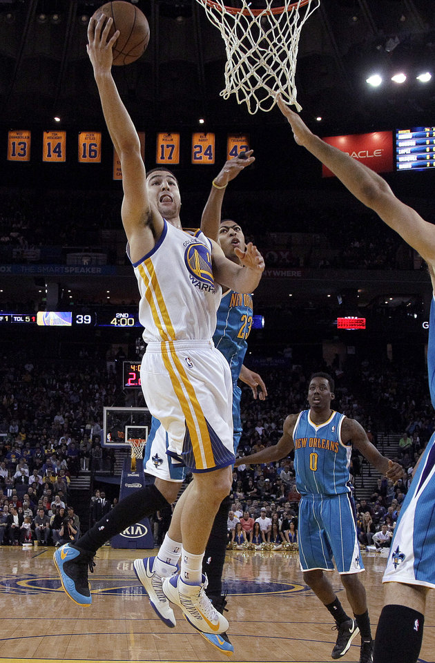 Photo - Golden State Warriors guard Klay Thompson (11) shoots against New Orleans Hornets forward Anthony Davis (23) during the second quarter of an NBA basketball game in Oakland, Calif., Wednesday, April 3, 2013. (AP Photo/Jeff Chiu)