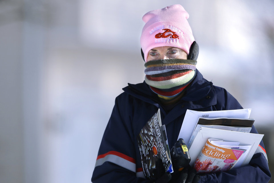 Photo - U.S. Postal Service letter carrier Jamie Jasmon struggles through snow and below zero temperatures while delivering the mail Monday, Jan. 6, 2014, in Springfield, Ill. A whirlpool of frigid, dense air known as a