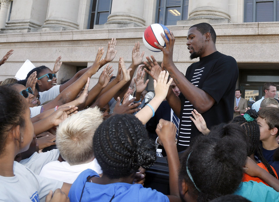 Photo -  Oklahoma City Thunder's Kevin Durant, gets greeted from students at an event at the state Capitol as part of an initiative to battle childhood obesity in Oklahoma City, Friday, Sept. 26, 2014. The Republican governor and Durant danced Friday before hundreds of Oklahoma students, parents and teachers on the north steps of the state Capitol to launch the governor's Get Fit Challenge. (AP Photo/Sue Ogrocki)